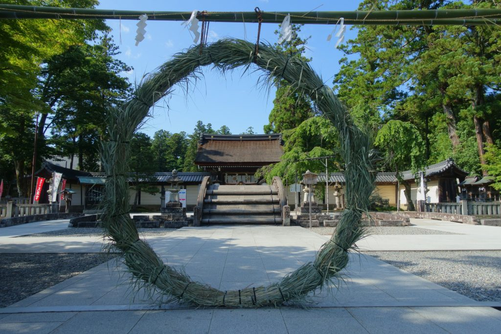 A huge straw ring large enough for a person to enter it is displayed vertically in front of a shrine.