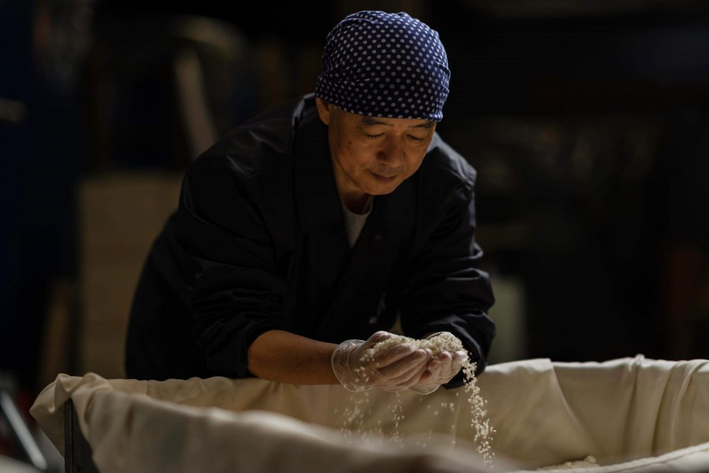 Keisuke is checking rice that he carefully holds in both hands