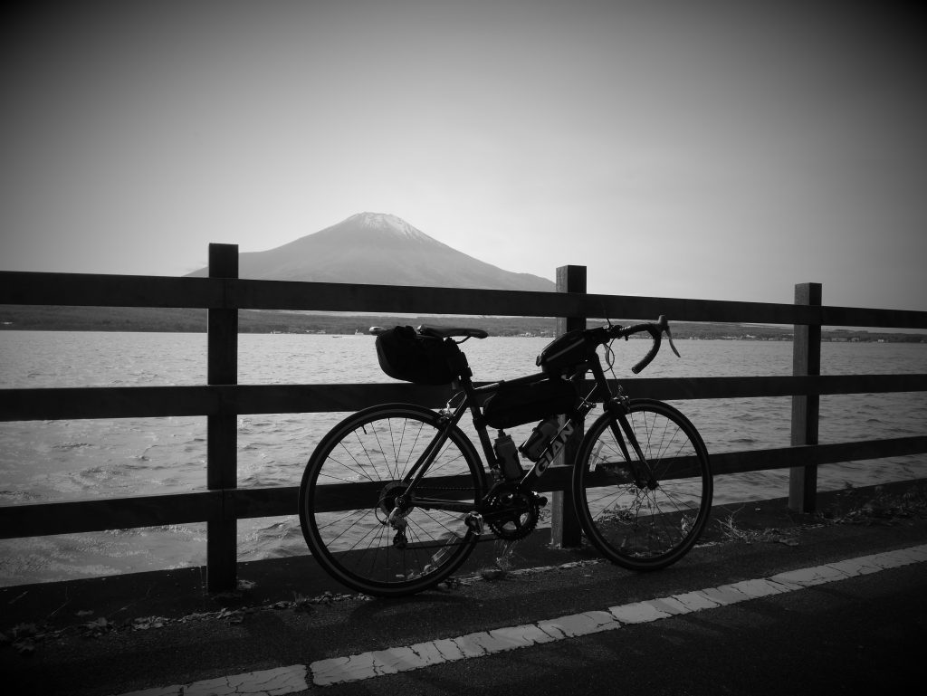 A bicycle in front of a lake. In the back, Mount Fuji.