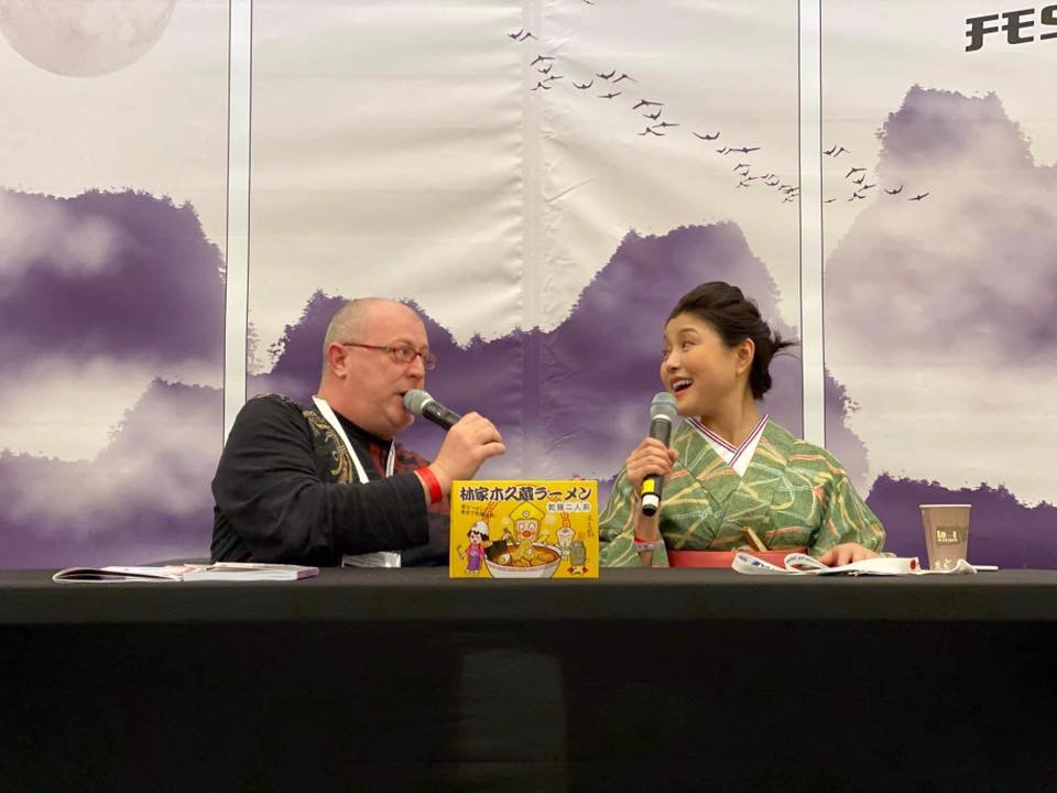 Cyril Coppini and Kikuhime Hayahsiya are sitting behind a desk and speaking in microphones.