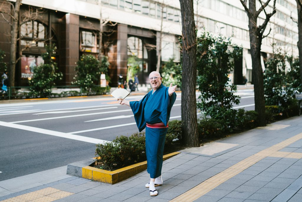 Cyril is posing on an avenue in Tokyo with his folding fan