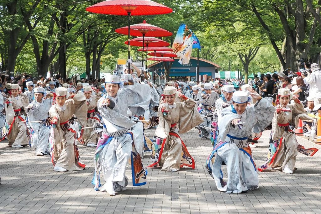A team of dancers in vivid costumes are dancing in the street,