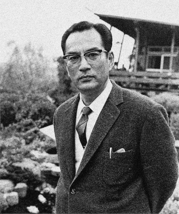 Black and white picture of a Japanese man in an elegant suit and glasses