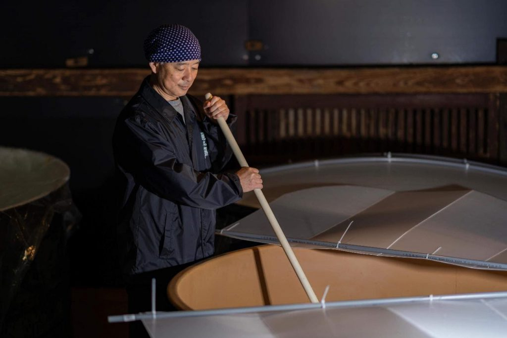 Keiseuke is using a wooden stick to mix the contents of a barrel