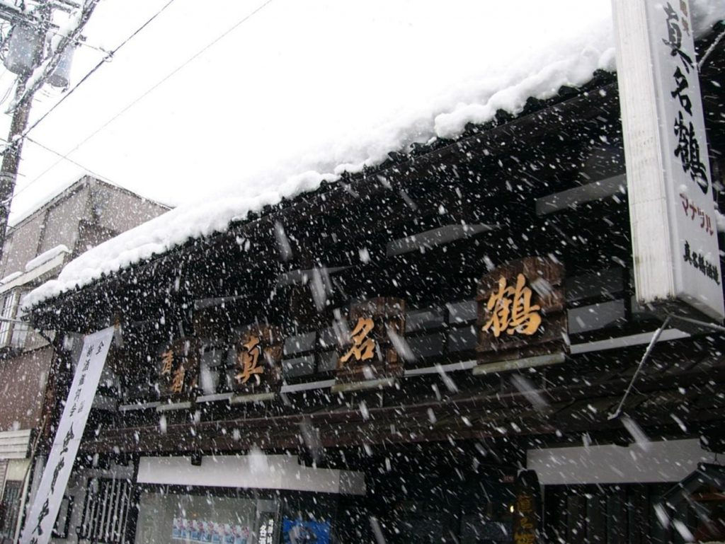 A traditional Japanese building under the snow
