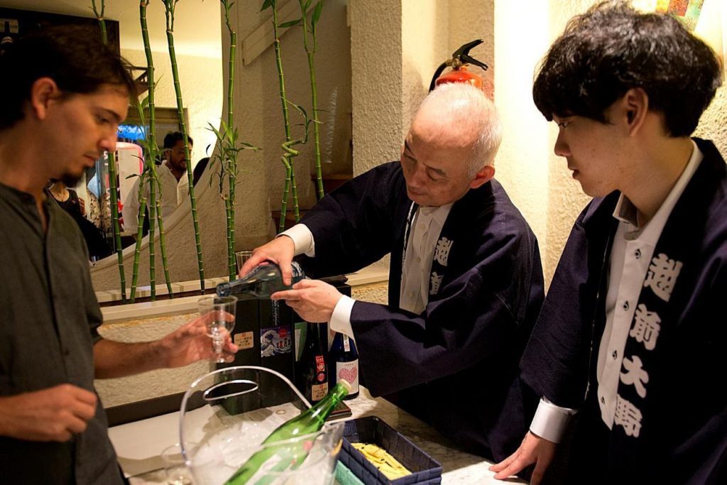 Keisuke and Rui are serving sake for clients to taste