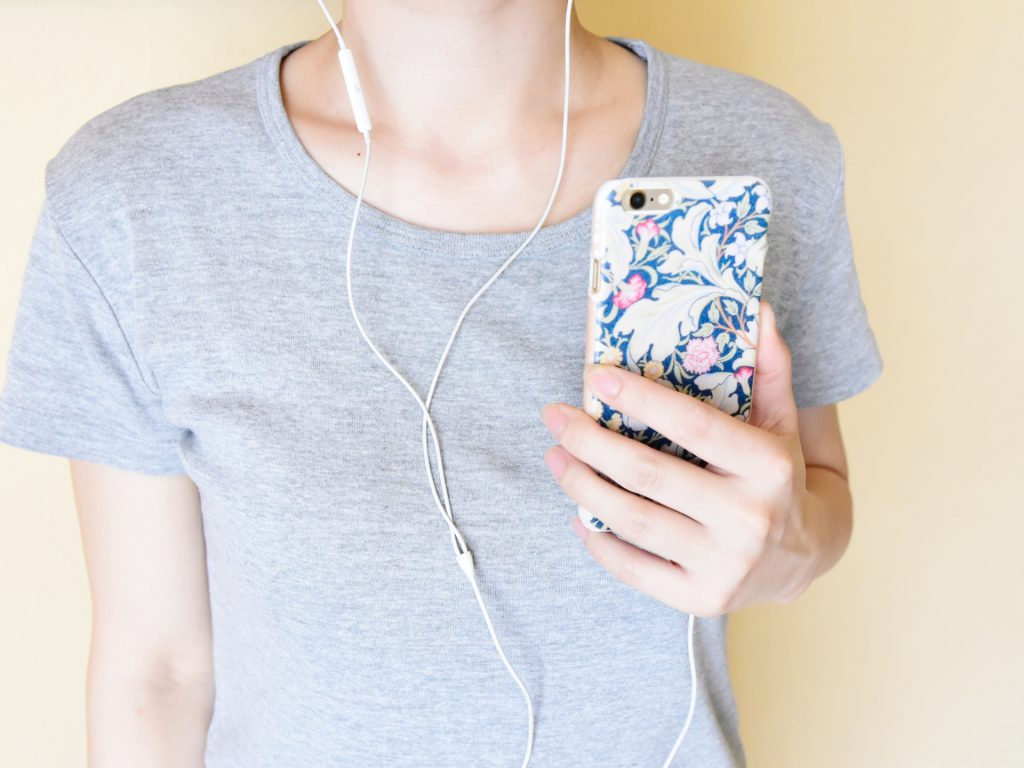 A woman with earphones linked to her smartphone