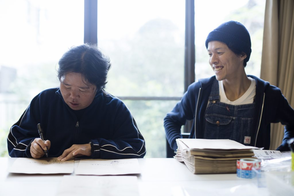 Go is smiling, sitting next to a woman who is writing on a paper