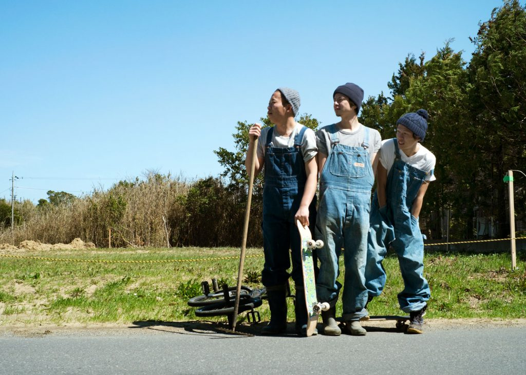 Go  with two other men. They are dressed in denim overalls and have their skateboards and BMX with them.