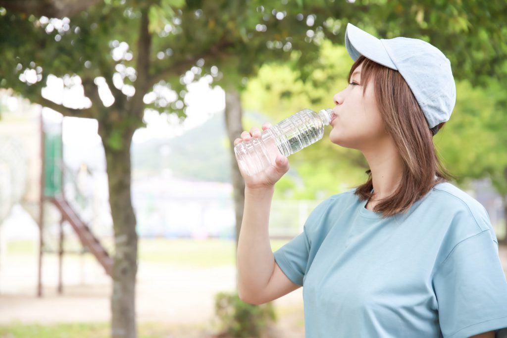A Japanese woman is drinking a bottle of water
