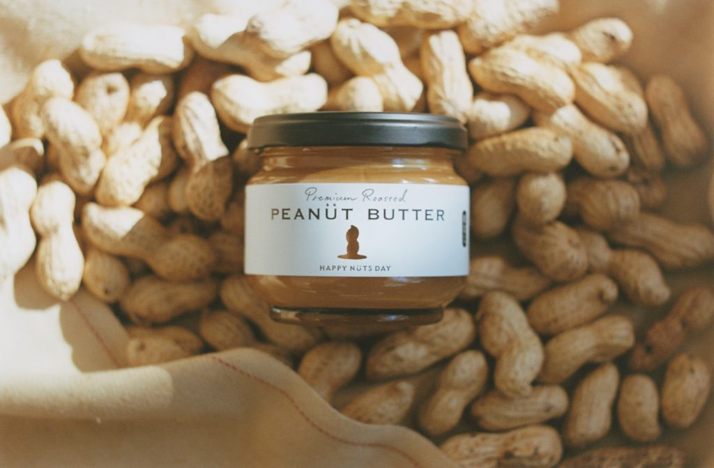 A pot of peanut butter lays on peanut shells