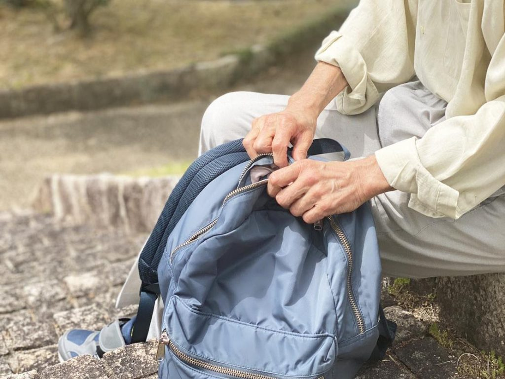 Hands of an elderly person are closing a bagpack