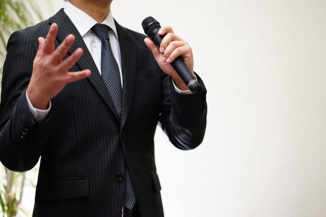 A man dressed in a suit is speaking in a microphone