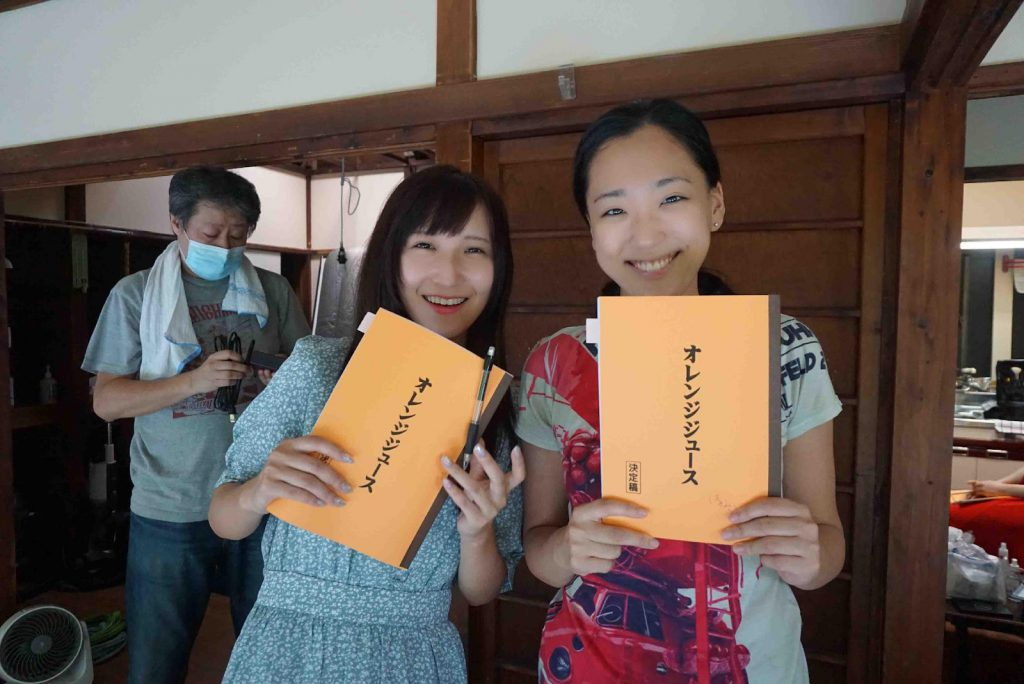 Two actresses are holding booklets and smiling to the camera