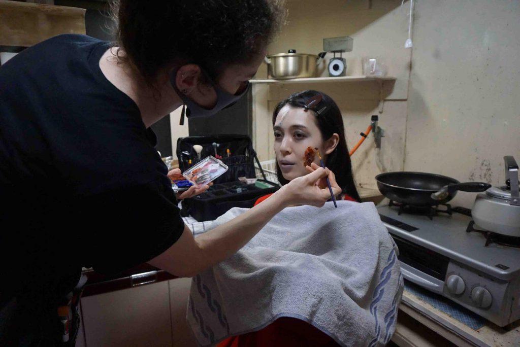 Faiza is applying bloddy-looking makeup on Kyoko's face