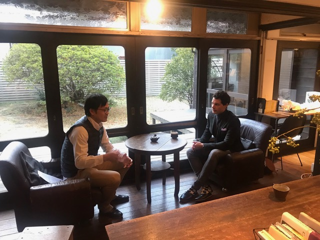 Two men are talking in a nice cafe